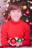 Glücklicher Kinderjunge, der Weihnachtsdekorationen hält Stockfoto