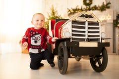 Glücklicher Kinderjunge spielt mit dem Spielzeugauto der Kinder auf Hintergrund des Weihnachtsbaums stockfoto