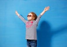 Glücklicher Kindermädchentourist in der rosa Sonnenbrille an der blauen Wand Reise- und Abenteuerkonzept Lizenzfreies Stockbild