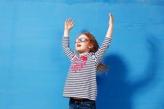 Glücklicher Kindermädchentourist in der rosa Sonnenbrille an der blauen Wand Reise- und Abenteuerkonzept Lizenzfreies Stockfoto