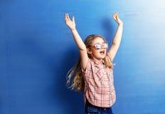 Glücklicher Kindermädchentourist in der rosa Sonnenbrille an der blauen Wand Reise- und Abenteuerkonzept Stockfotos