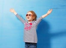 Glücklicher Kindermädchentourist in der rosa Sonnenbrille an der blauen Wand Reise- und Abenteuerkonzept Stockfotografie