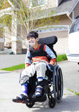 Glücklicher kleiner behinderter Junge im Rollstuhl Stockbild