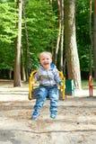 Glücklicher kleiner blonder Junge, der Spaß auf einem Schwingen hat Stockfotografie