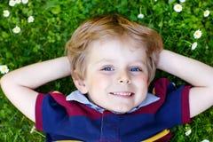 Glücklicher kleiner blonder Junge mit den blauen Augen, die auf das Gras legen Stockbild