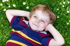 Glücklicher kleiner blonder Junge mit den blauen Augen, die auf das Gras legen Stockfotos