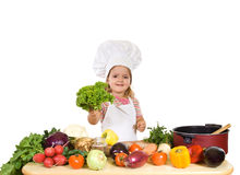 Glücklicher kleiner Chef mit Lots Gemüse Stockfotos