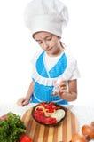 Glücklicher kleiner Chefkoch salzt Salat lizenzfreie stockfotografie