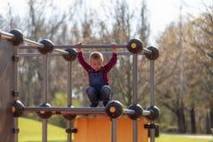 Glücklicher kleiner Junge auf kletterndem Rahmen des Kinderspielplatzes lizenzfreies stockbild