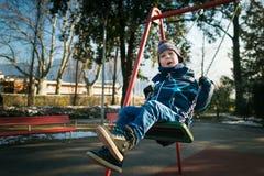 Glücklicher kleiner Junge auf Schwingen Stockbild
