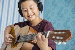 Glücklicher kleiner Junge, der übt, um Akustikgitarre zu spielen Stockfotos