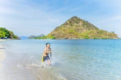 Glücklicher kleiner Junge, der auf dem rosa Strand läuft Stockfotos