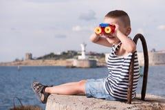 Glücklicher kleiner Junge, der den Abstand durch bunte Ferngläser untersucht Lizenzfreies Stockbild