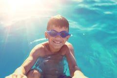 Glücklicher kleiner Junge, der draußen Schwimmbadrand hält stockfoto
