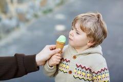 Glücklicher kleiner Junge, der Eiscreme, draußen isst Stockfotos