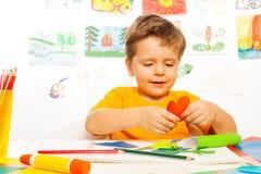 Glücklicher kleiner Junge, der geformten Karton des Herzens in Handarbeit macht Lizenzfreie Stockfotografie