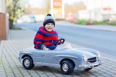 Glücklicher kleiner Junge, der großes Spielzeugauto fährt und Spaß, draußen hat Lizenzfreie Stockfotografie