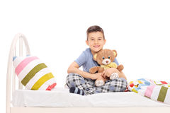 Glücklicher kleiner Junge, der im Bett sitzt und einen Teddybären umarmt Stockfotografie