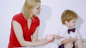 Glücklicher kleiner Junge, der Münzen mit Mutter zählt Wie man reiches gefälschtes Buch erhält stock video