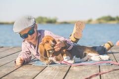 Glücklicher kleiner Junge, der mit seinem Hund durch den Fluss liegt lizenzfreies stockfoto
