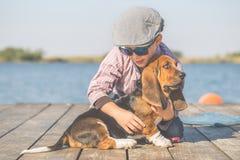Glücklicher kleiner Junge, der mit seinem Hund durch den Fluss spielt stockfoto