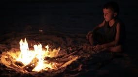 Glücklicher kleiner Junge, der nahe dem Feuer sitzt stock video