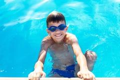 Glücklicher kleiner Junge, der Rand des Swimmingpools hält stockfotografie