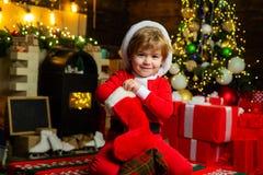 Glücklicher kleiner Junge, der sein Geschenk von den Weihnachtssocken nimmt Konzept des neuen Jahres Sch?ne vektorabbildung stockfotografie