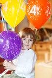 Glücklicher kleiner Junge, der seins Geburtstag 4 mit buntem balloo feiert stockfotografie