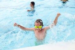 Glücklicher kleiner Junge, der Spaß im Swimmingpool hat Stockbilder