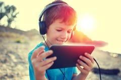 Glücklicher kleiner Junge, der Spiel auf Tablette in der Natur spielt stockfotografie