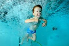 Glücklicher kleiner Junge, der unter Wasser im Pool in den Wasserstrahlen auf blauen Hintergrund und dem Lächeln schwimmt und spi stockbilder