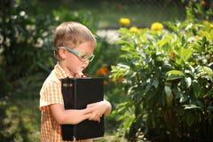 Glücklicher kleiner Junge des Porträts, der ein großes Buch an seinem ersten Tag zur Schule oder zur Kindertagesstätte hält Drauß Stockfoto