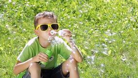 Glücklicher kleiner Junge des Porträts, der im Park sitzt stock video