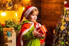 Gl?cklicher kleiner Junge durch den Weihnachtsbaum mit seinem Weihnachtsgeschenk Kleinkind tr?gt Sankt-Kleidung Weihnachtsniederl stockfoto
