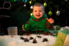 Glücklicher kleiner Junge hält Weihnachtsball in der Hand, sitzt und lächelt stockbild