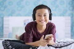 Glücklicher kleiner Junge hören Musik im Schlafzimmer Stockfoto