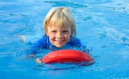 Glücklicher kleiner Junge hat Spaß mit sich hin- und herbewegendem Brett im Swimmingpool Stockbild