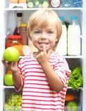Glücklicher kleiner Junge mit dem grünen Apfel, der seins zeigt stockbild