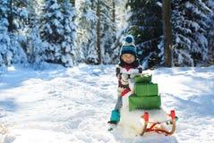 Glücklicher kleiner Junge mit dem hölzernen Schlitten voll von den Geschenkboxen Stockfoto