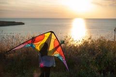Glücklicher kleiner Junge mit Drachen hinter Schultern auf Sommerseesonnenunterganghintergrund Lizenzfreies Stockbild