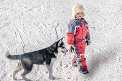 Glücklicher kleiner Junge mit Hündchenschlittenhund auf dem Schnee Stockbild