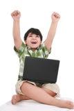 Glücklicher kleiner Junge mit Laptop Stockfotos