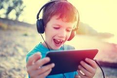 Glücklicher kleiner Junge mit Tablette lachend Weinlese im Freien lizenzfreie stockfotos