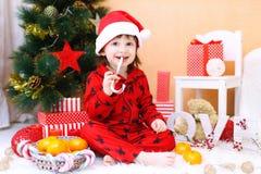 Glücklicher kleiner Junge in Sankt-Hut mit Lutscher und Geschenken sitzt Ne Lizenzfreie Stockfotografie