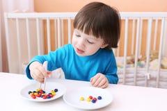 Glücklicher kleiner Junge spielt mit Scheren und Perlen Pädagogisches playi Lizenzfreies Stockbild