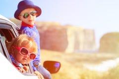 Glücklicher kleiner Junge und Mädchen reisen mit dem Auto herein Stockbild