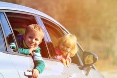 Glücklicher kleiner Junge und Mädchen reisen mit dem Auto in Natur Lizenzfreie Stockfotografie