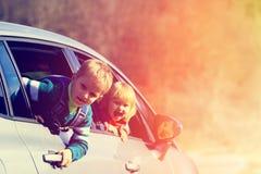 Glücklicher kleiner Junge und Mädchen reisen mit dem Auto in Natur Stockfotografie