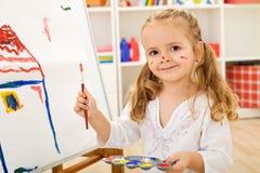 Glücklicher kleiner Künstler - Mädchen, das ein Haus malt Stockfotografie